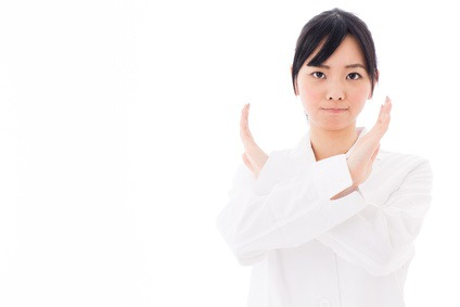 両手でバツ印をしている女性の画像